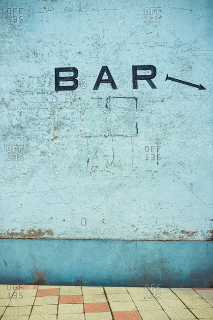 Old blue cement wall with scratches on surface and BAR inscription with painted arrow near tiled floor in daylight