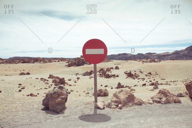 Prohibitory round red no entry road sign with white rectangle across placed on rural sandy desert terrain on hot day one way traffic