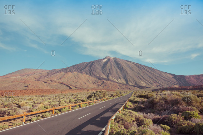 Asphalt roadway with marking lines passing between dry barren terrain near mountains under picturesque blue sky with clouds in afternoon