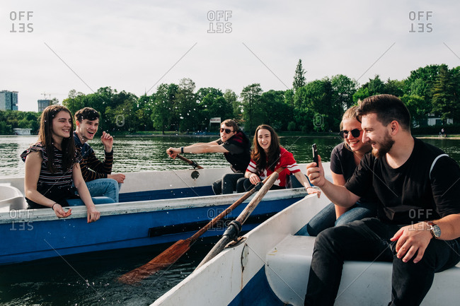 Positive laughing young friends chilling on boats and browsing mobile phone while spending weekend together on peaceful tranquil pond in Saint George, Transylvania, Romania