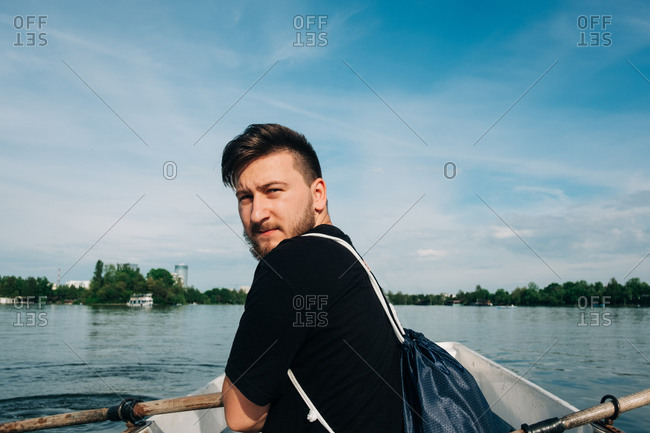 Back view of bearded male in casual black outfit rowing boat by using oars on calm picturesque lake and looking at camera in Saint George, Transylvania, Romania