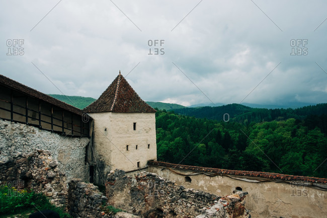 Picturesque scenery of ancient castle located on grassy hilltop against majestic green highlands under gloomy sky of Saint George, Transylvania, Romania
