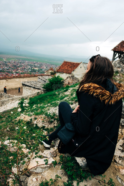 Side view full body unrecognizable calm female in outerwear sitting on high viewpoint and admiring amazing scenery of old town on overcast day in Saint George, Transylvania, Romania