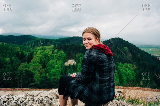 Side view smiling young female in warm jacket sitting on rocky hill against majestic green grassy highlands and looking down over shoulder on cloudy day in Saint George, Transylvania, Romania