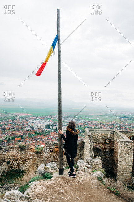 Back view full body female traveler standing near flagpole with Romanian national flag located at high viewpoint against scenic old city in Transylvania on cloudy day