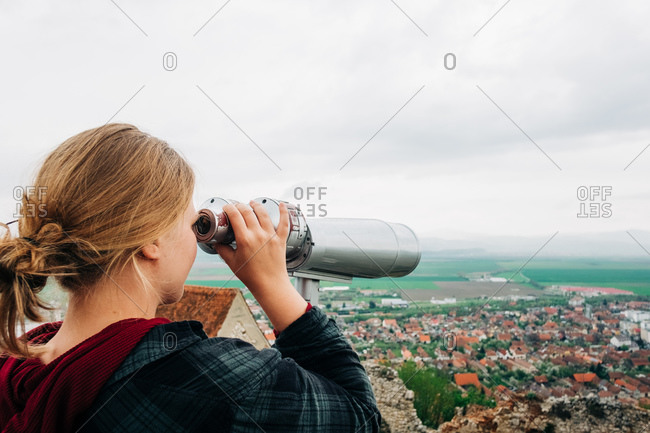 Back view unrecognizable female in casual wear enjoying view of old city while looking in stationery panoramic binoculars on observation deck in Transylvania Romania