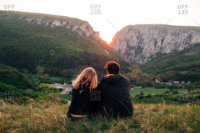 Back view of unrecognizable couple of tourists standing on background of mountain range and tenderly embracing while enjoying holiday in Transylvania