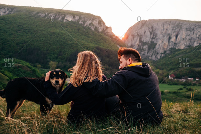 Back view of loving couple hugging on meadow with fluffy dog while relaxing on background of majestic mountains during holiday in Transylvania