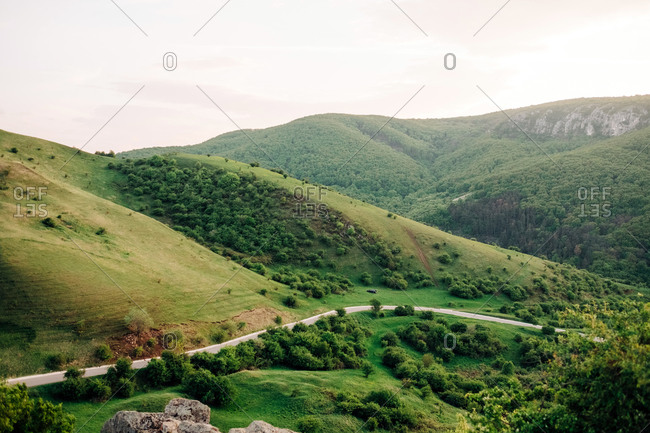 Spectacular landscape of road in mountains covered with green woods on background of sunset sky in Transylvania