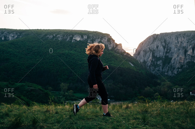 Side view of plump female in sportswear running along green meadow on background of amazing landscape of highlands during sundown in Transylvania