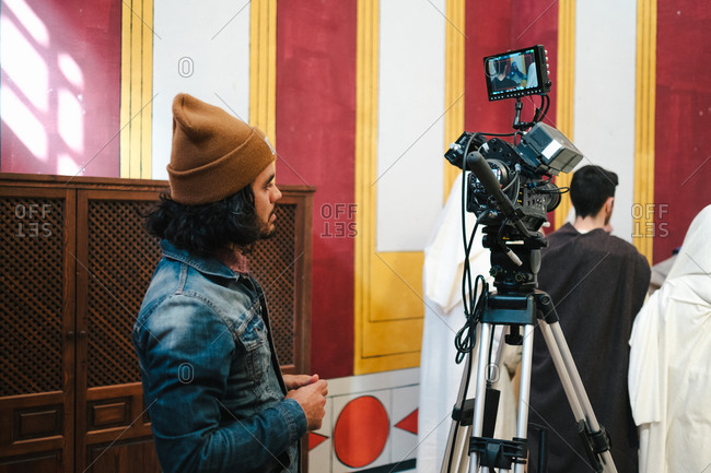 Side view focused male videographer in denim jacket and hat standing nearby professional video camera during short break in creative studio
