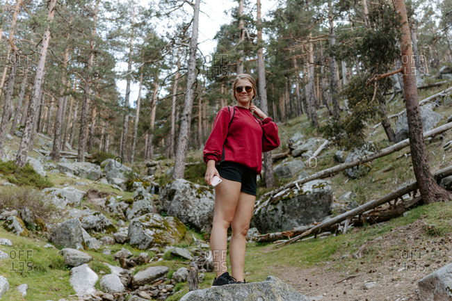 Low angle full length of young female hiker in sunglasses with smartphone in hand standing on stone and looking at camera during trekking in forest in Navacerrada in Spain