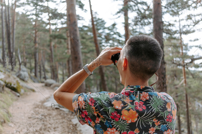 Back view of male tourist in colorful shirt standing on slope of mountain covered with coniferous forest and observing environment with binoculars during hiking in Navacerrada in Spain