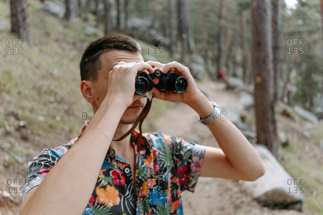 Male tourist in colorful shirt standing on slope of mountain covered with coniferous forest and observing environment with binoculars during hiking in Navacerrada in Spain