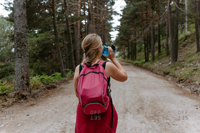 Back view of active young female backpacker standing on pathway among green forest and drinking water while resting during trekking in Navacerrada in Spain
