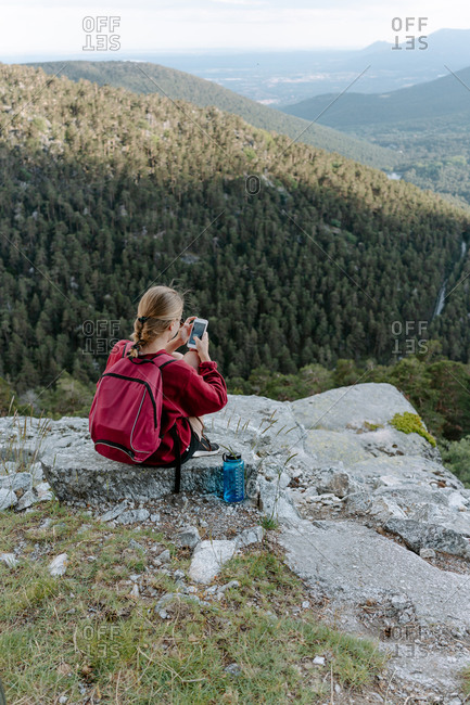 Back view of young female traveler with backpack sitting on stone and checking pictures on smartphone while resting during hiking in picturesque mountains in Navacerrada in Spain