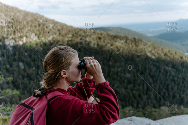 Side view of young female backpacker sitting on stony top of mountain and exploring scenery with binoculars while resting after climbing in Navacerrada in Spain
