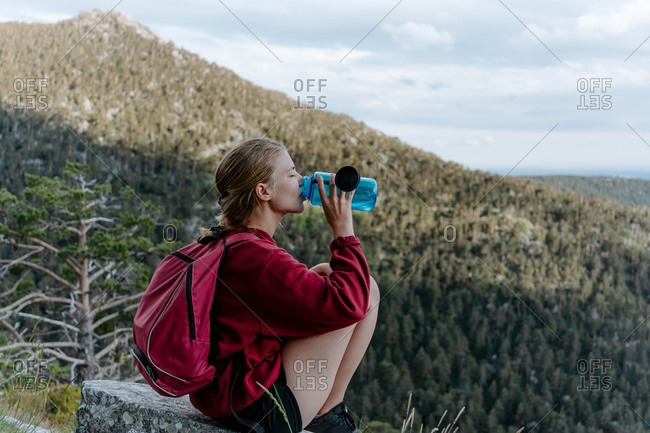 Side view of young female backpacker sitting on stone against green forested hill and drinking water while resting during hiking in Navacerrada in Spain