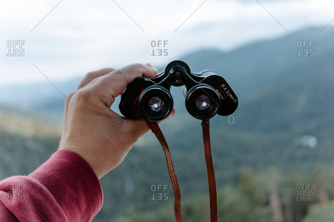 Crop anonymous hiker holding binoculars while observing nature in mountainous terrain in summer day