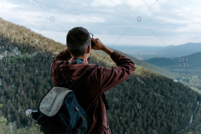 Back view of unrecognizable male tourist with backpack standing on mountain slope and admiring view of green hills while observing landscape with binoculars in Navacerrada in Spain