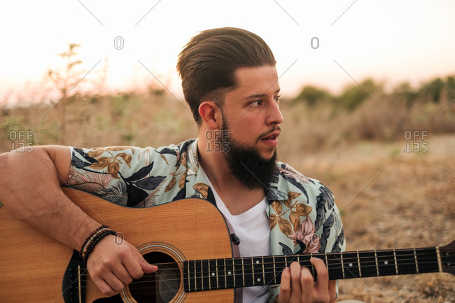 Smiling hipster male musician in casual wear playing classic guitar while sitting on rug near faded grass under serene sky in evening