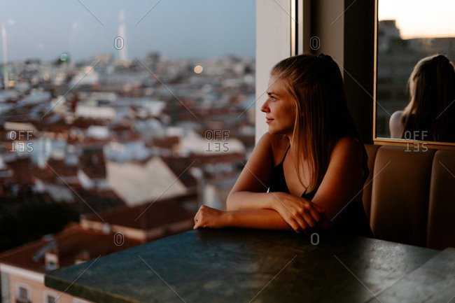 Side view of young female traveler sitting in cozy cafe on rooftop of city building and admiring view of evening Madrid through glass window looking away