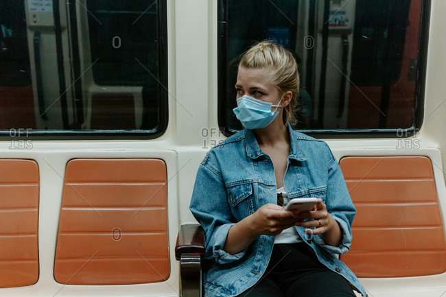 Millennial female passenger in casual outfit and protective mask browsing mobile phone while sitting alone inside underground train with prohibition signs on seats for keeping distance during coronavirus pandemic