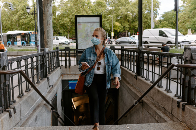 Young female in casual outfit and protective mask using smartphone while walking up subway staircase on city street