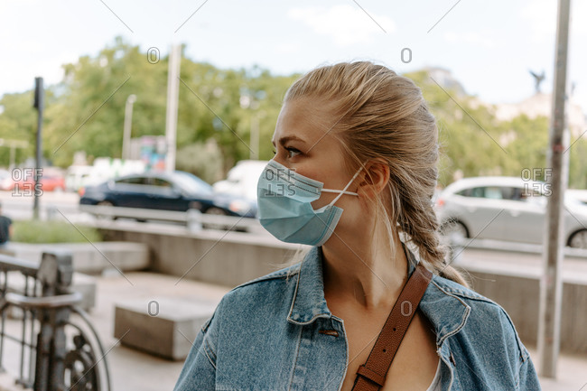 Young female in casual outfit and protective mask walking on city street looking away
