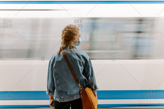 Back view of millennial female passenger in protective mask and casual denim jacket with handbag standing on underground platform in front of moving train