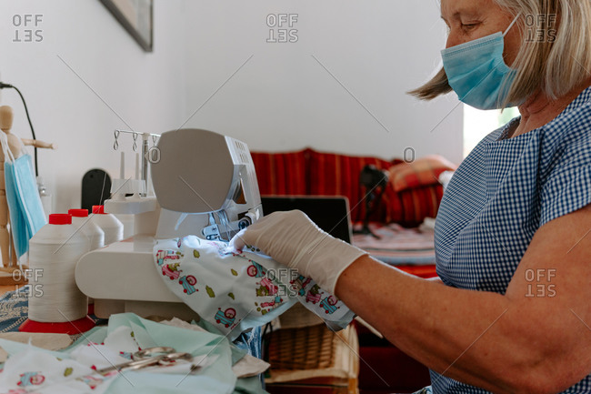 Side view of elderly female artisan in medical mask and gloves sewing masks for coronavirus protection with colorful fabric while sitting at workplace with sewing machine and tools at home