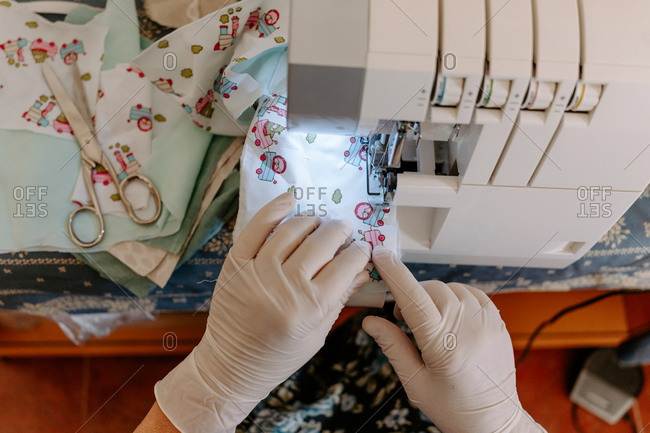 From above crop unrecognizable seamstress on latex gloves sewing fabric masks for coronavirus prevention at workplace
