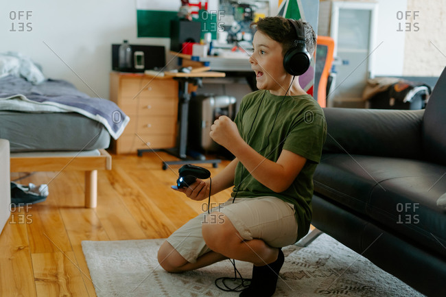 Side view of excited little boy in casual clothes and headphones celebrating victory while playing video game with joystick on floor at home