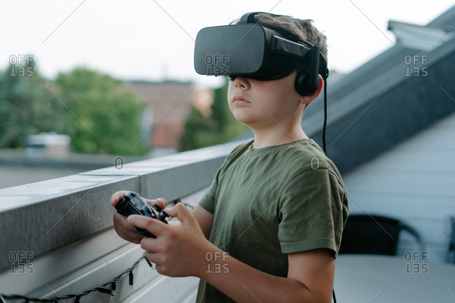 Curious little boy in t shirt standing on balcony alone and looking away using VR goggles and joystick