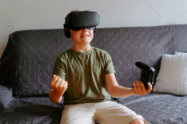 Adorable little boy experiencing virtual reality in modern goggles while playing on sofa with gamepad at home