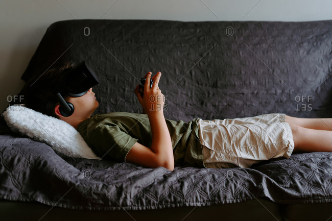 Side view of concentrated child in casual clothes lying on sofa with gamepad and enjoying VR goggles device