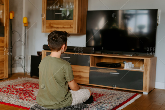 Back view of unrecognizable child in casual wear sitting on floor with legs crossed and watching TV