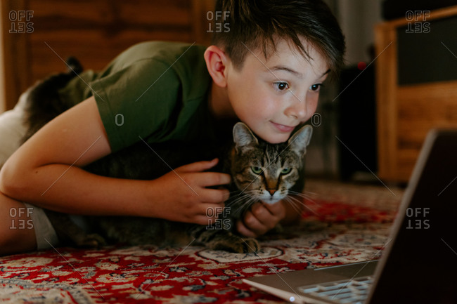 Cheerful adorable kid cuddling cat and having fun while sitting on floor and watching video on laptop