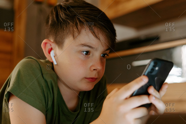 Concentrated little boy in t shirt and true wireless earphones lying on carpet at home and watching video on smartphone during summer vacation
