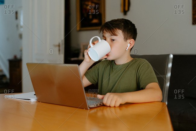 Concentrated little boy in wireless earphones drinking hot beverage while sitting at table with laptop during online lesson