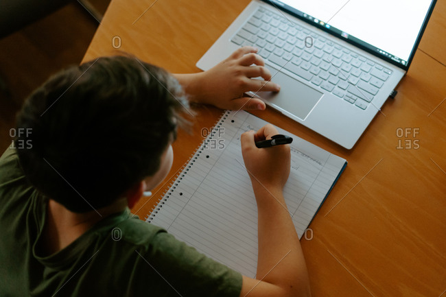 High angle of focused little boy in wireless earphones using laptop and writing down information while doing homework assignment