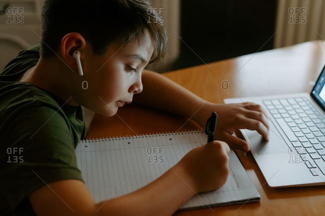 Side view of focused little boy in wireless earphones using laptop and writing down information while doing homework assignment