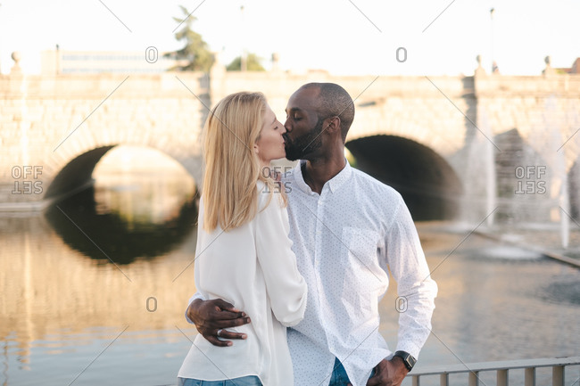 Loving diverse couple in casual outfits embracing and kissing while standing against beautiful stone bridge on sunny day
