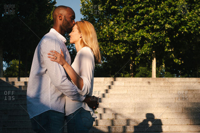 Full body side view content multiethnic couple embracing and kissing while standing face to face against staircase on sunny evening street in Madrid Spain