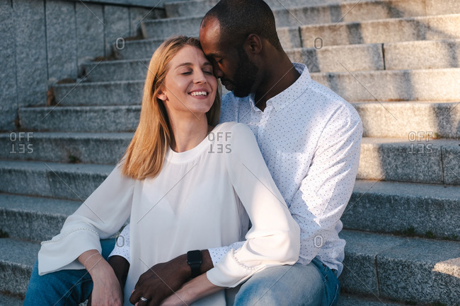 Content black boyfriend sitting on street stairs behind smiling girlfriend while bonding sensually and cuddling together in daytime