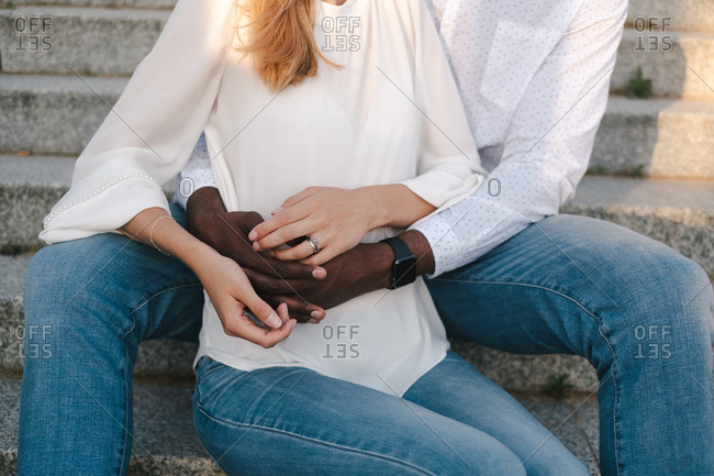 Crop faceless multiethnic couple bonding and holding hands together while African American boyfriend sitting on street stairs behind girlfriend