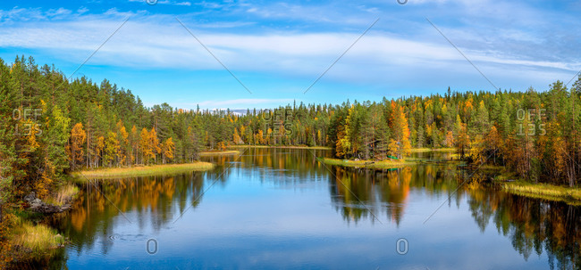 Peaceful lake surrounded by forest with colorful trees reflecting in water against bright blue sky