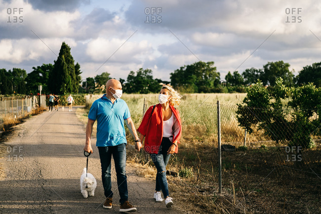 Full length positive adult couple in protective face masks wearing casual outfits strolling with funny Bichon Frise dog on lead along rural road and metal fence on cloudy summer day