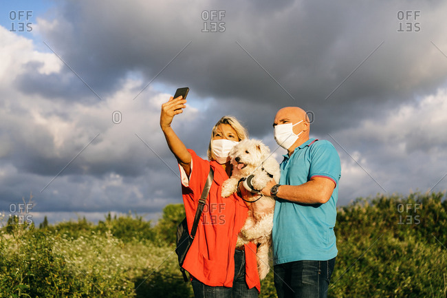 Content adult couple in face masks wearing casual summer clothes standing with adorable white Bichon Frise dog on hands and taking selfie on mobile phone while spending evening in nature