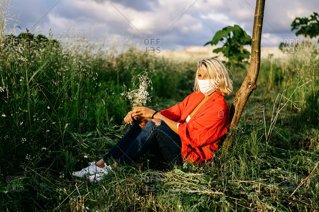 Side view full body calm female in casual clothes resting on grassy ground against thin tree trunk and looking away in peaceful nature during coronavirus epidemic